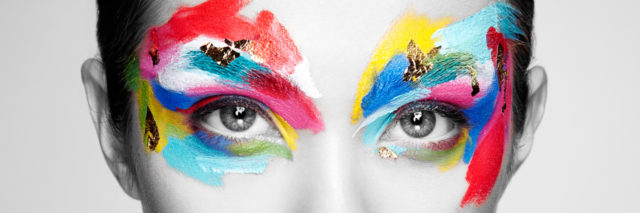 black and white photo of woman with colorful makeup around her eyes