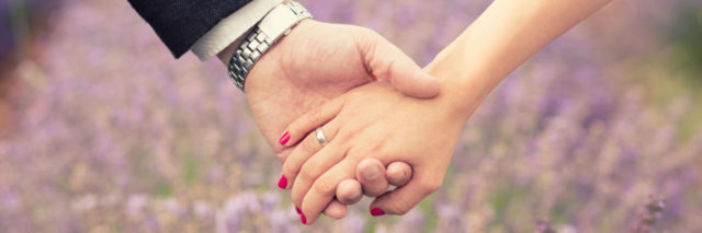 husband and wife holding hands in front of a field of flowers