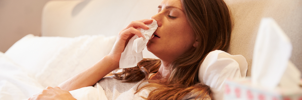 woman blowing her nose while sick in bed