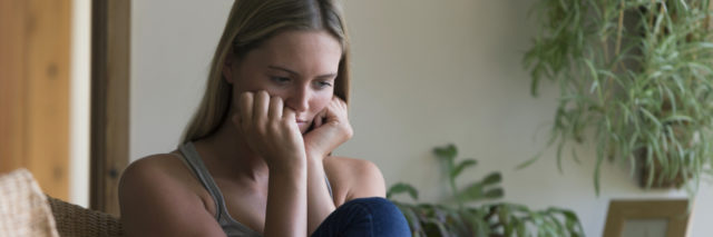 woman sitting at home looking upset with head in hands next to tablet