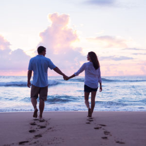 couple holding hands and walking on the beach at sunset