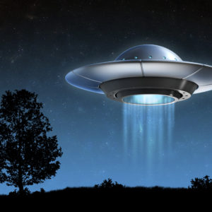 Alien spaceship hovering over land.