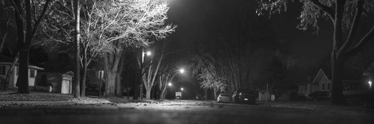 Black and white photograph of street in the United States, with lights illuminating parts of it. Taken at night.