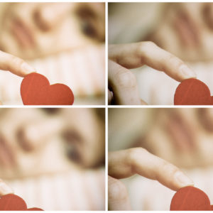 Sad girl holding heart symbol by her finger.