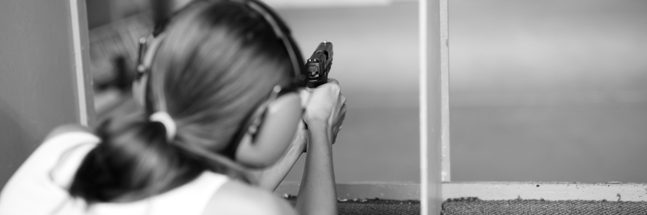 black and white photo of woman at gun range with handgun