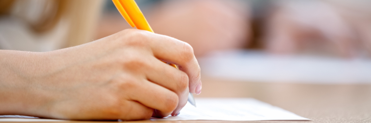 Student writing on paper at desk in classroom