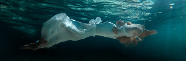 Woman in white dress swimming under water in the pool.