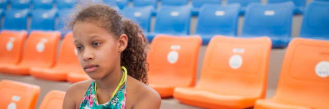 Depressed African American teenager sitting on a stadium and watching her favorite sports team loosing a game.