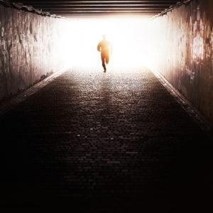 person running through a dark tunnel toward the sun
