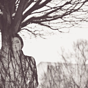 double exposure of woman and tree branches