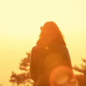 Woman wearing jacket, walking, facing sunset
