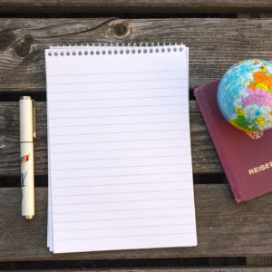 pad of paper next to a passport and mini globe
