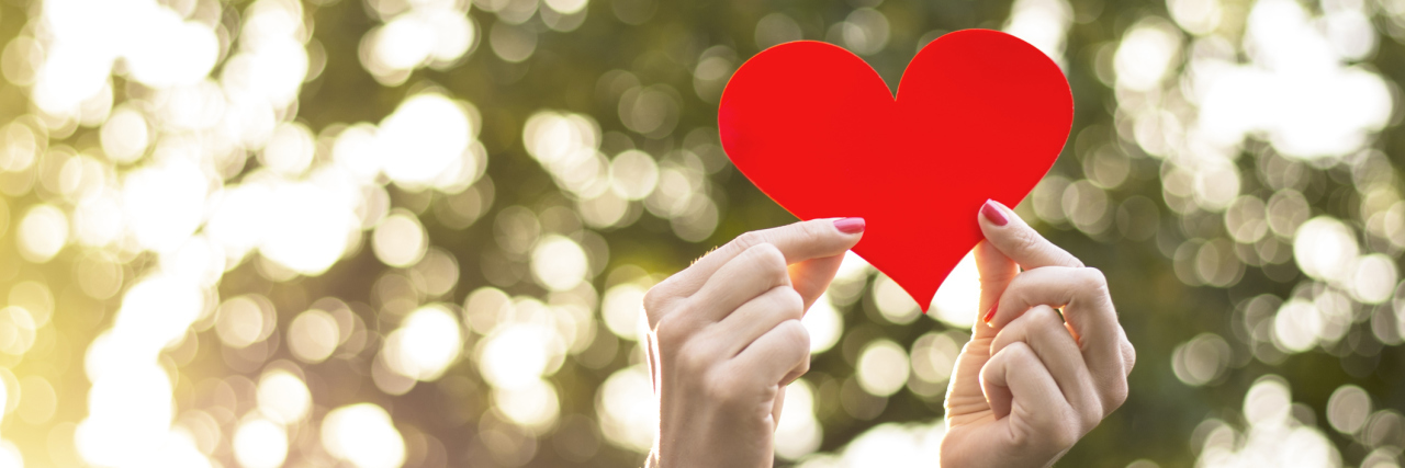 Woman holding red heart in her hands