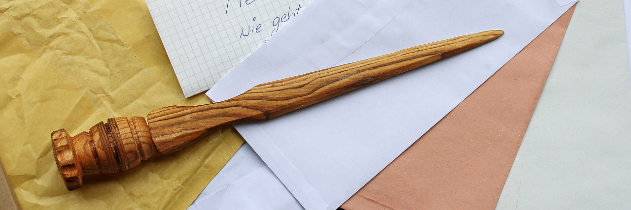 A letter opener in wood and open mail.