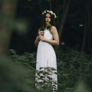 A woman in the woods, wearing a white dress.