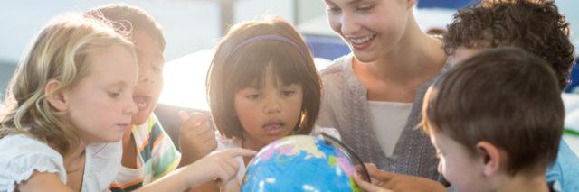 Teacher looking at schoolchildren touching globe.