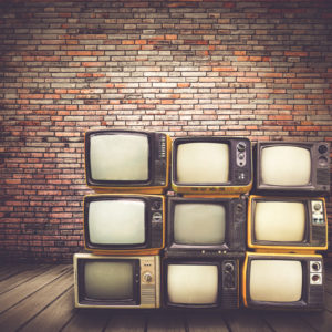 Vintage style TVs stacked on one another, in front of a brick wall.