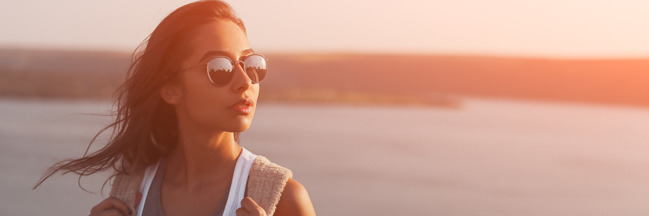 A woman wearing sunglasses, with a sunset and body of water behind her.