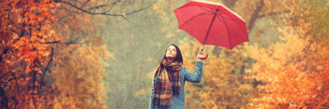 A young woman with a red umbrella walking through a park in the fall.