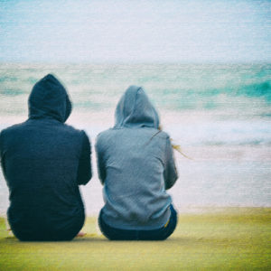 Two teenagers sitting on the beach.