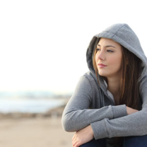woman in a gray hoodie sitting near the beach looking into the distance