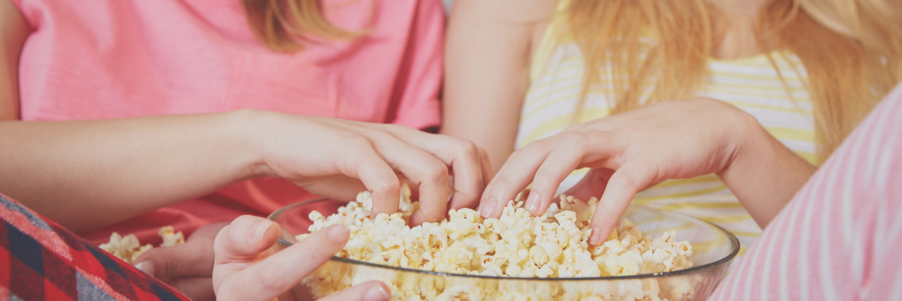 Young women eating popcorn watching movie.