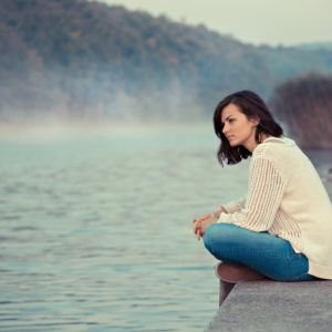 woman sitting on a pier looking at a lake