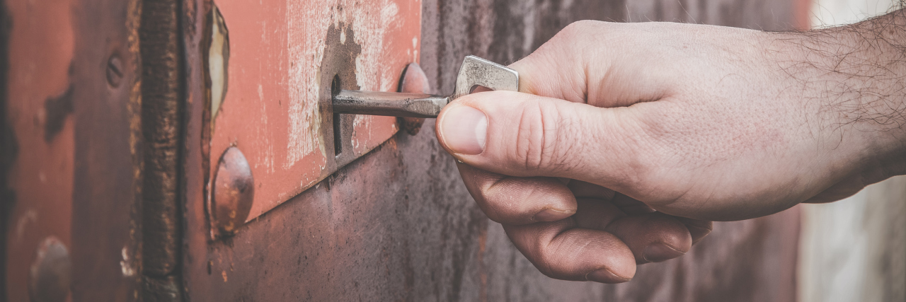 A man locking a door with a skeleton key.