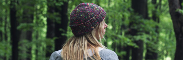 woman in a beanie walking outside in a forest