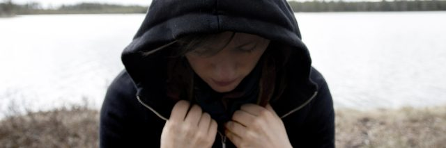 Woman in a black hoodie standing with the back towards a lake. She is looking down and has a shadow over her face. Concept photo of depression, mental illness and loneliness.