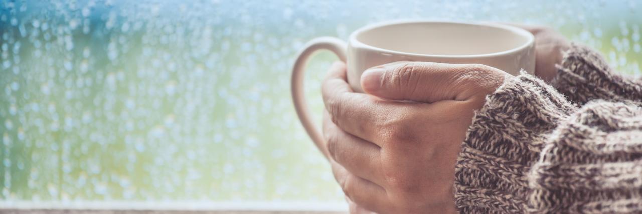 woman holding a mug of tea on a rainy day