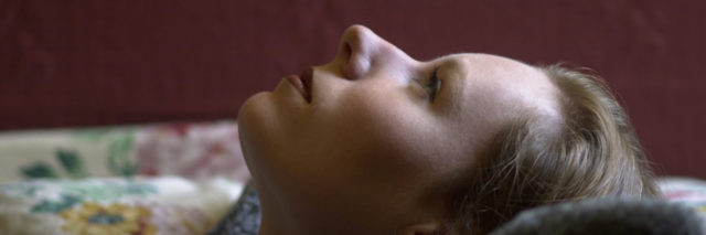 woman lying on her back in bed staring at the ceiling