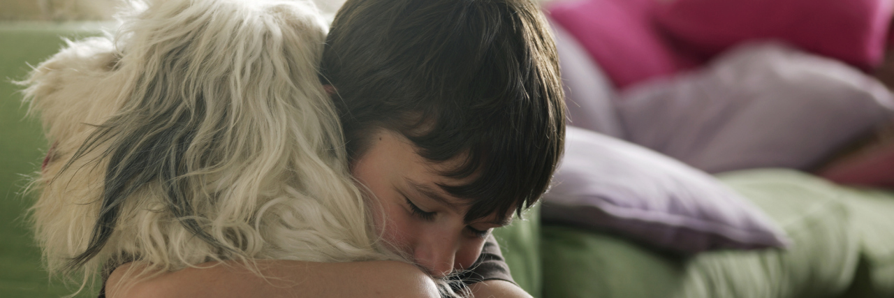 Boy hugging his dog.
