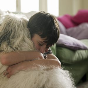 Boy hugging his dog.