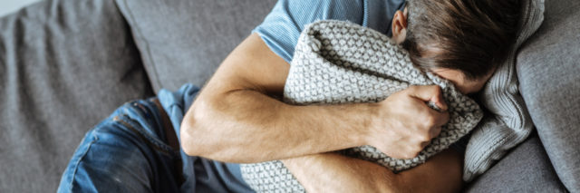upset man lying on sofa hugging pillow crying