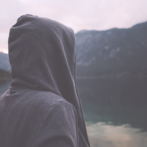 woman wearing a hoodie and standing outside near a lake