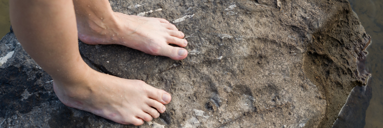 woman standing barefoot on a rock