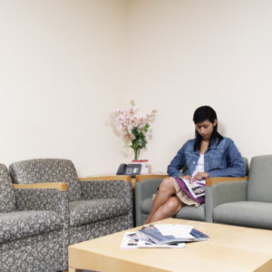 woman sitting in the waiting room of a doctor's office