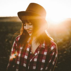 young smiling woman at sunset in field