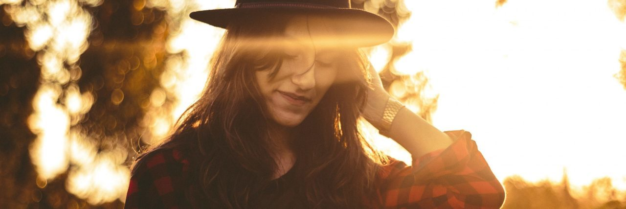 dark haired woman wearing hat smiling sunset