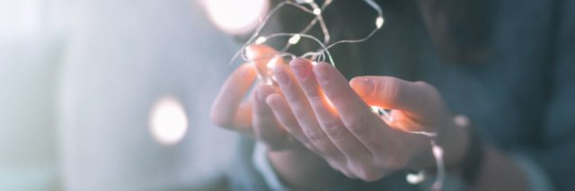 young woman's hands holding fairy lights in delicate way