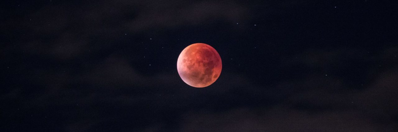 red moon with clouds and stars