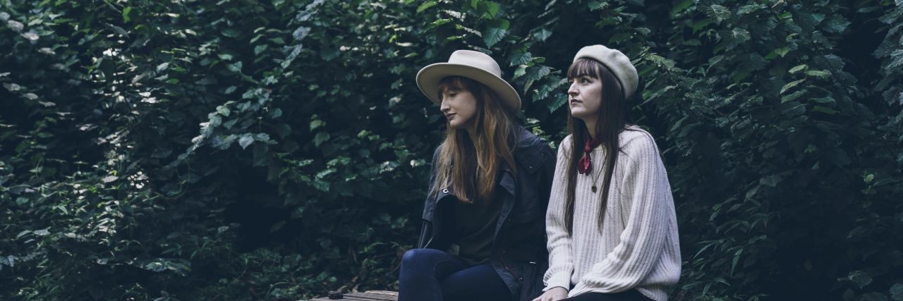 two woman sit together on a bench in the fall