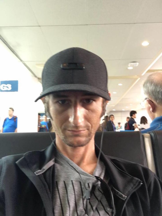man sitting in an airport wearing a hat