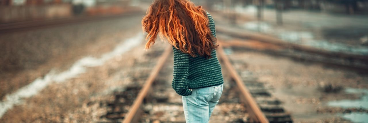 redhead woman standing on train tracks looking contemplative