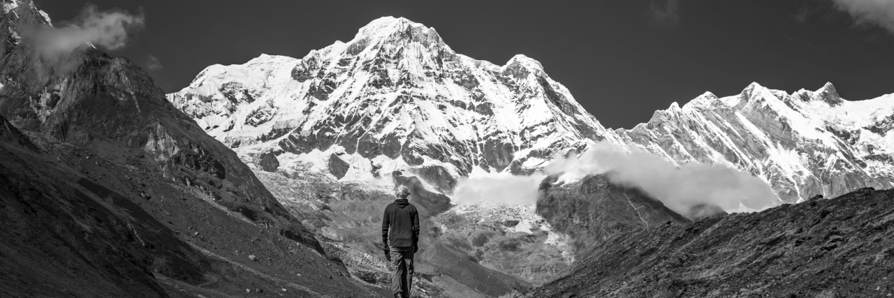 person standing in front of himalayan mountains in black and white