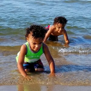 Twin boys playing in the tide at the beach.