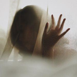 woman behind white curtain