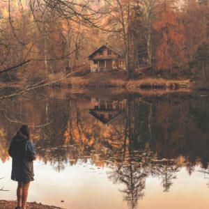 woman standing by river in autumn with reflection of trees