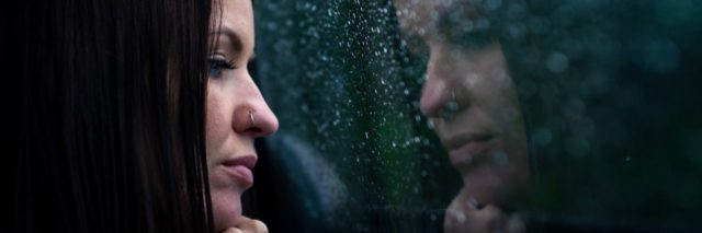 woman with dark hair looking out of rainy window and reflection